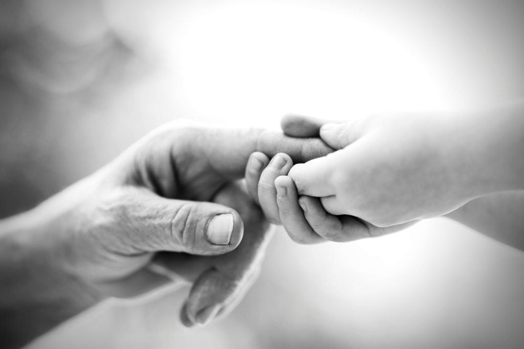 baby hand holding adult hand - reduced
