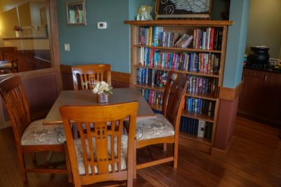 soft seating arrangement at one dining table, bookcase, flowers